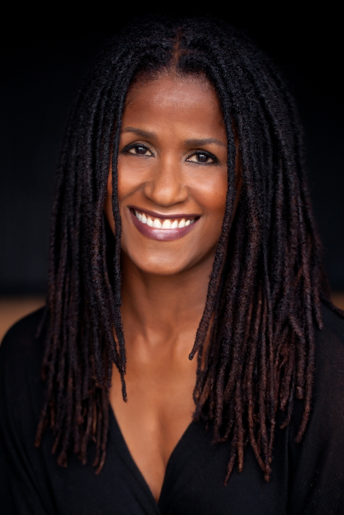 Image of Bahni Turpin, a Black woman with long dread locs smiling at the camera.